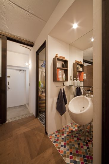 【リノベ暮らしな人々】洗面コーナー。楕円形の洗面ボウルに、床にはキッチンの壁と同じカラフルなタイルが敷かれている